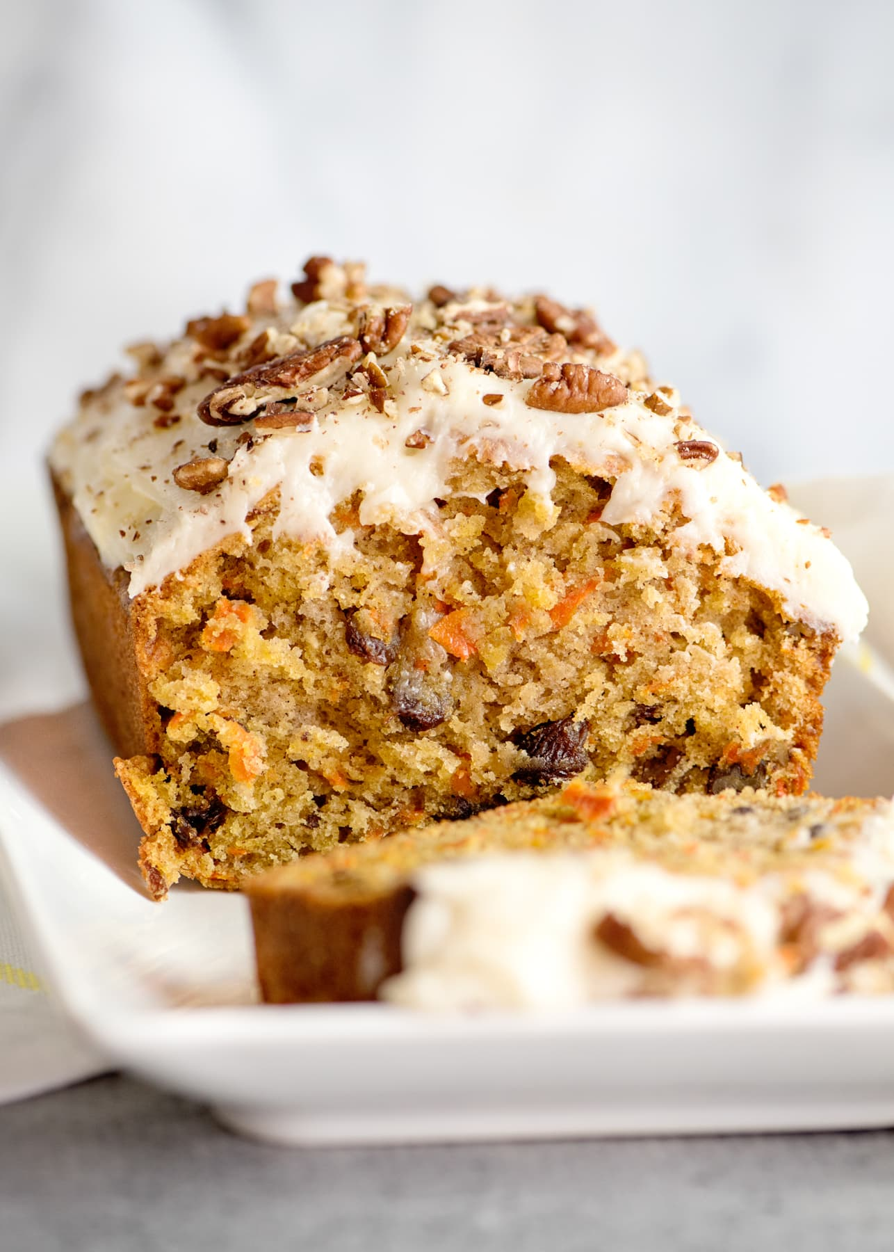 Carrot cake loaf with cream cheese frosting, topped with crushed pecans.