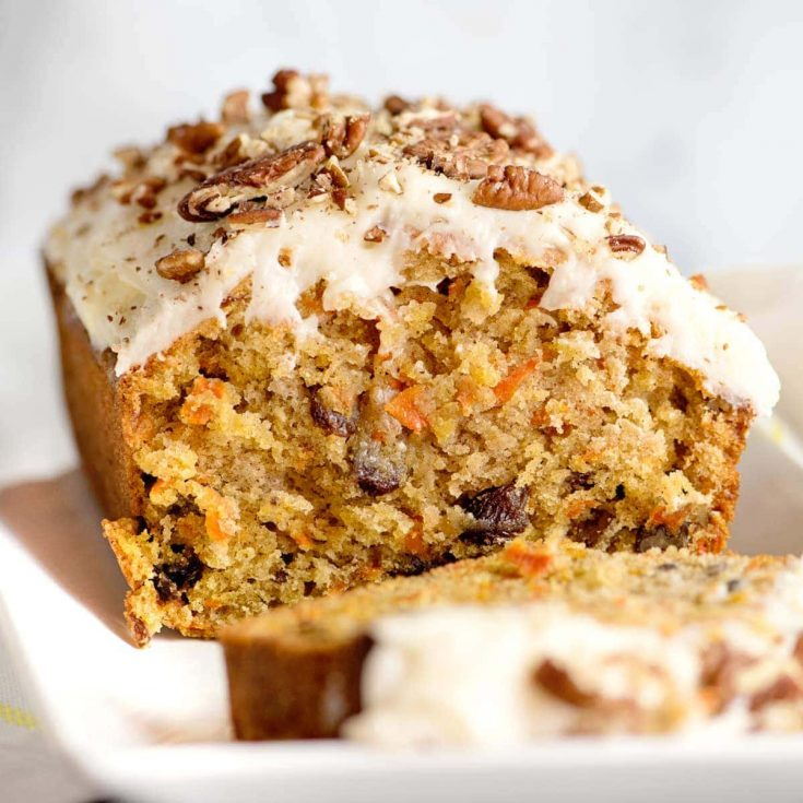 A loaf of carrot cake next to a slice, iced with cream cheese frosting and walnuts