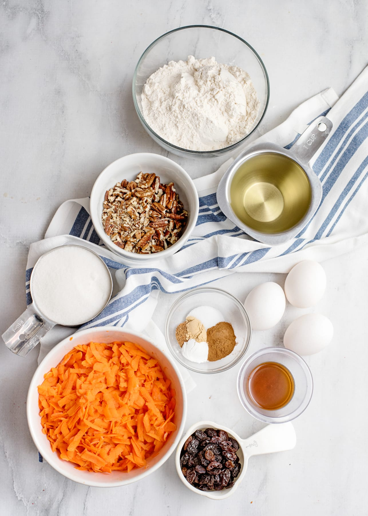 ingredients to make carrot cake loaf recipe, grated carrots, flour, eggs, oil, nuts and spices