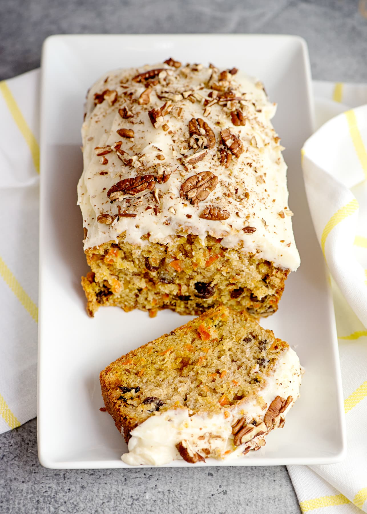 Carrot cake loaf with a cut slice, sitting on a plate iced with frosting
