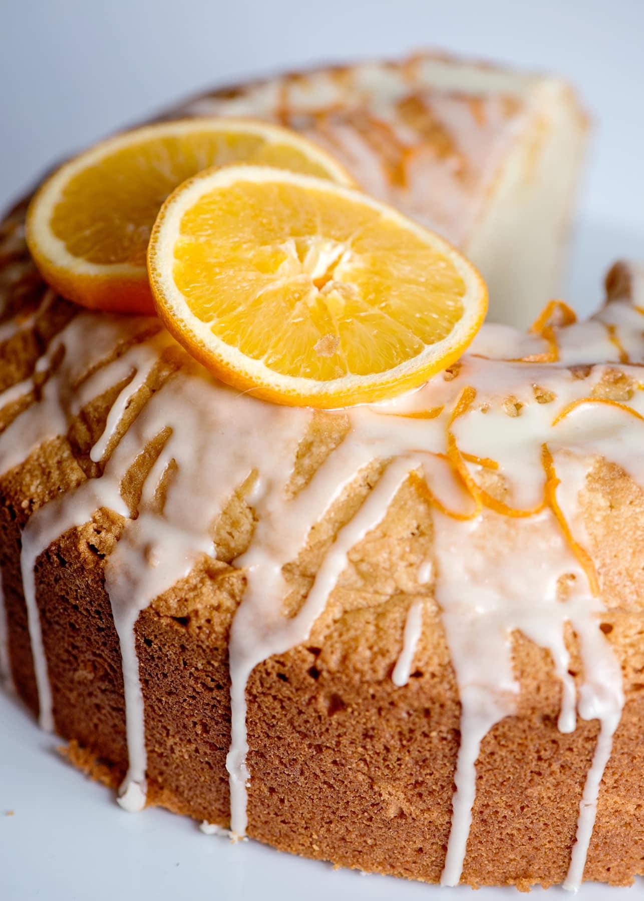 close up of orange pound cake with sliced oranges and glaze on top